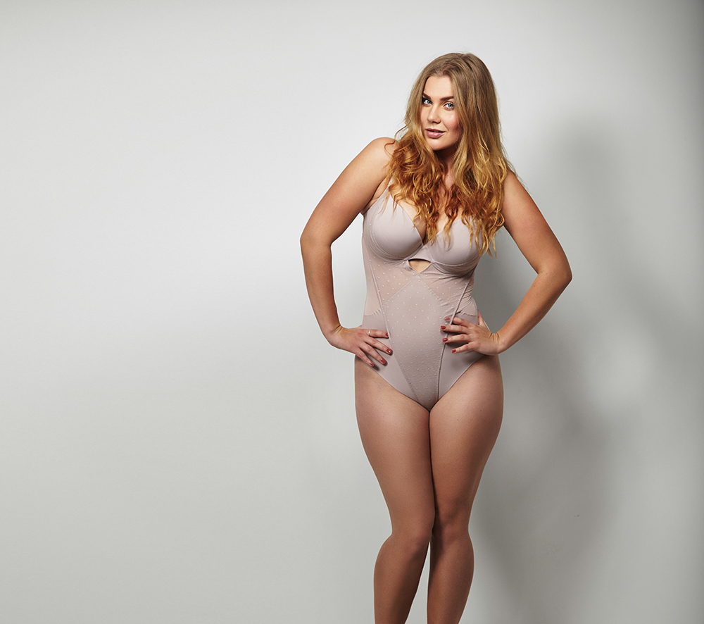 beautiful, curvy woman posing in body suit