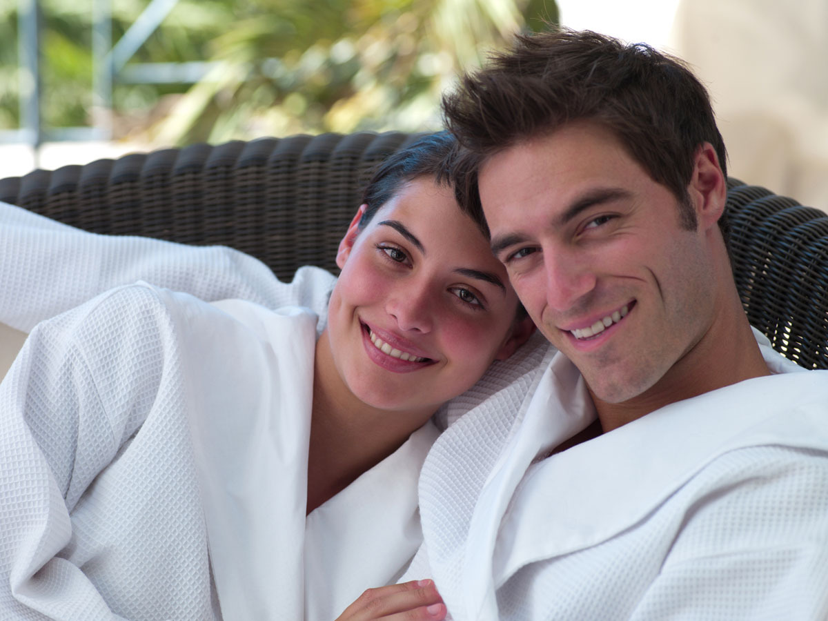 content and confident looking couple in bathrobes with full heads of hair