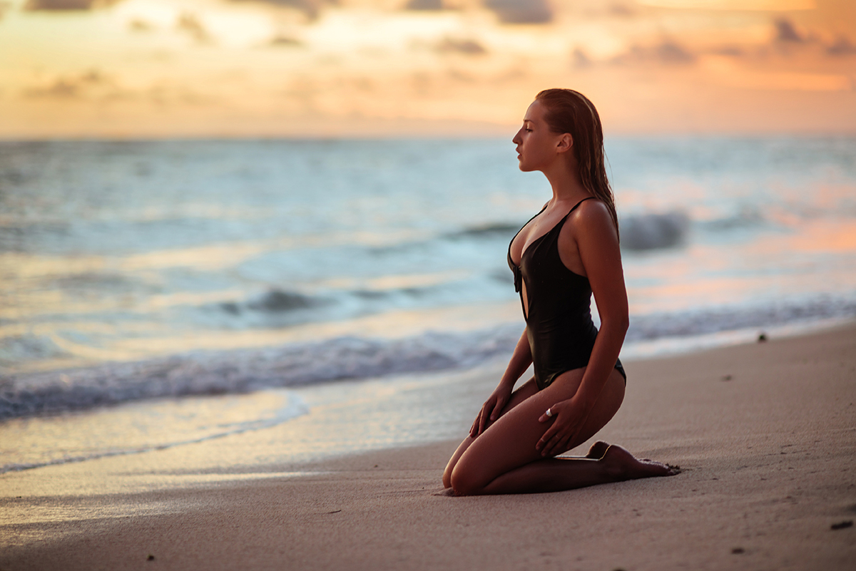 woman kneeling on beach looking out contemplatively