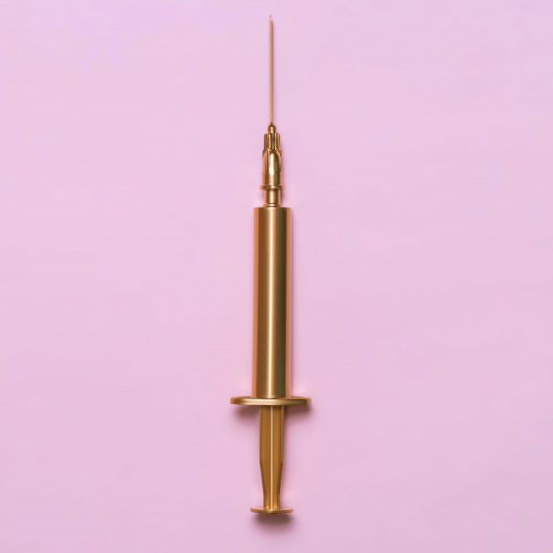 Golden syringe on a pink background