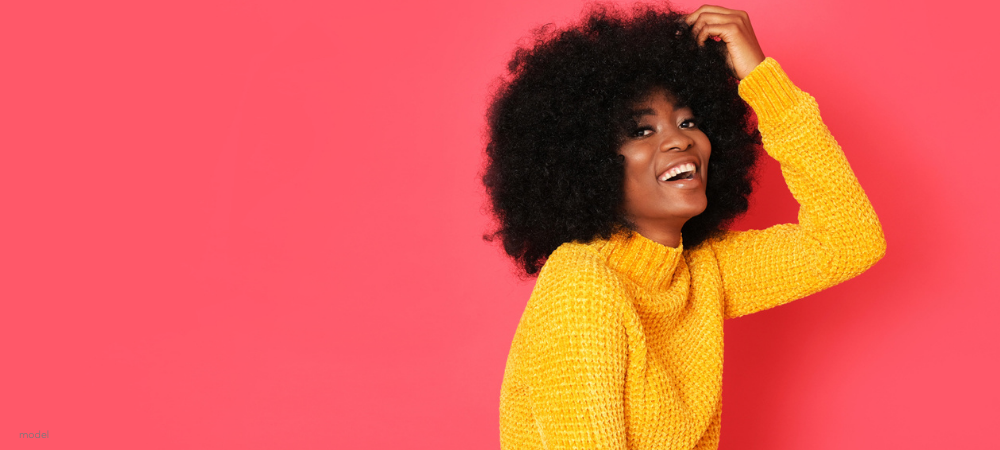 African-American Woman laughing on coral background
